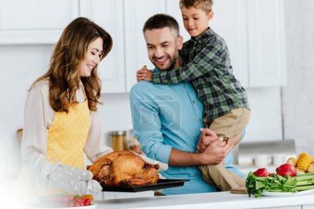 happy little kid with parents preparing thanksgiving turkey together at kitchen