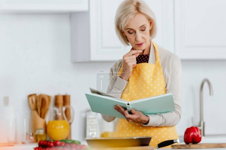 Seniorin liest Rezeptbuch beim Kochen in Küche