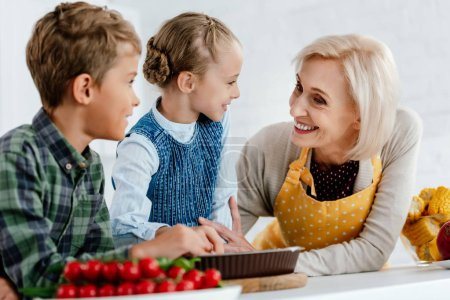 siblings making pie and having fun with grandmother at kitchen