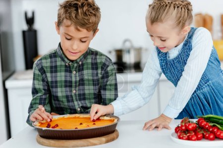 cute siblings decorating thanksgiving pumpking pie with berries together at kitchen