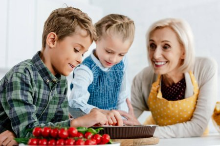 siblings making pie with grandmother at kitchen
