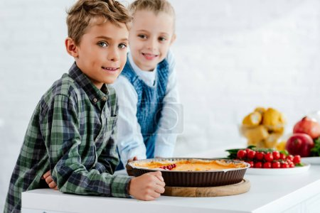 siblings with pumkin pie looking at camera together at kitchen