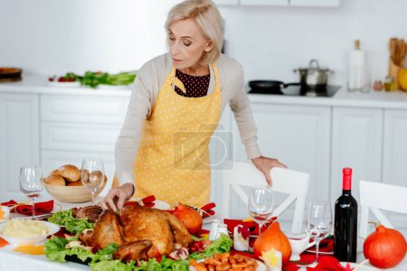 senior woman serving table for thanksgiving dinner in kitchen at home