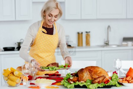 smiling senior woman carrying meal on table with delicious dishes for thanksgiving celebration