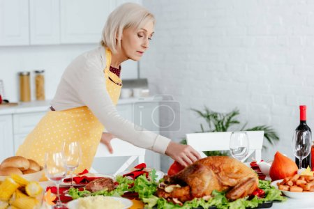 beautiful senior woman serving table for thanksgiving dinner in kitchen at home