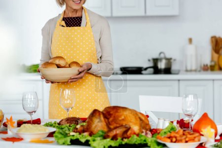 cropped image of smiling woman holding bowl with bread near served table for thanksgiving celebration