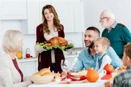 Photo for Beautiful smiling woman carrying baked turkey for thanksgiving dinner with family - Royalty Free Image