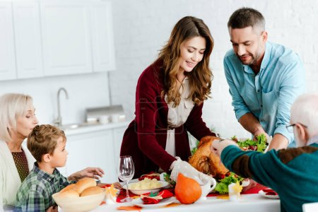 smiling adult couple carrying baked turkey for thanksgiving dinner with big family at home