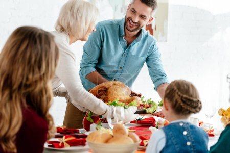grandmother carrying delicious baked turkey for thanksgiving dinner with family