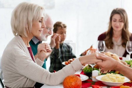 selective focus of grandmother praying with family at served table with turkey before holiday dinner on thanksgiving
