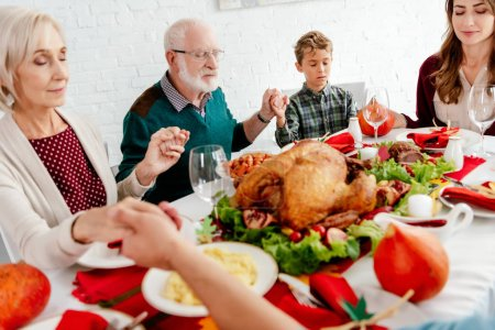 happy family holding hands and praying at served table with turkey before holiday dinner on thanksgiving