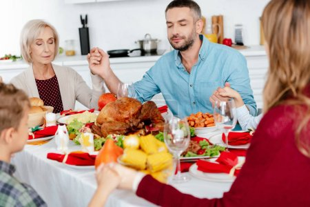 happy family praying at served table with turkey before holiday dinner on thanksgiving
