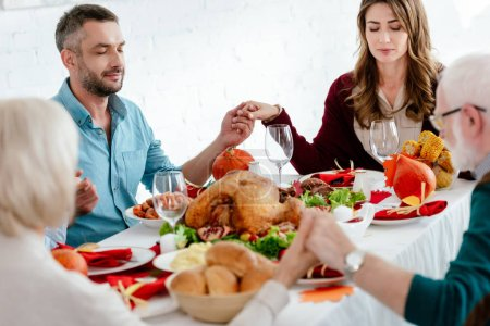 family praying at served table with turkey before thanksgiving celebration