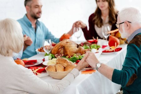 selective focus of family praying at served table with turkey before holiday dinner on thanksgiving