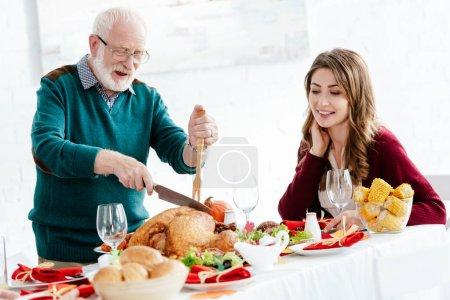 happy senior man slicing delicious turkey for thanksgiving celebration while his adult daughter sitting near at table