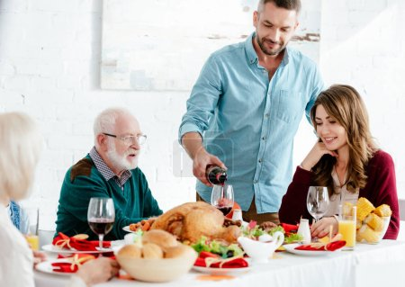 adult man pouring wine into glass at served table while family having thanksgiving celebration at home