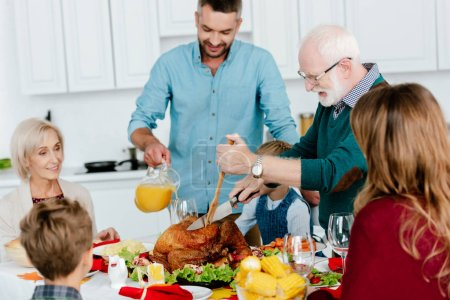 grandfather slicing baked turkey at served table while family celebrating thanksgiving