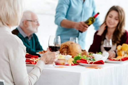 partial view of senior woman with wine glass celebrating thanksgiving with family at served table with turkey