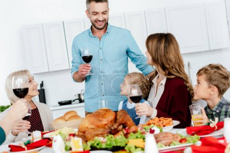 happy adult man with wine glass making toast at served table with turkey while his family celebrating thanksgiving