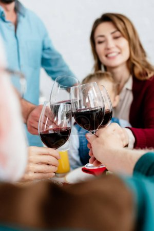 partial view of big family clinking with wine glasses and celebrating thanksgiving at served table