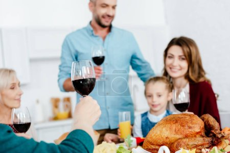 selective focus of family with wine glasses celebrating thanksgiving at served table
