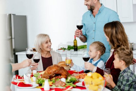 partial view of adult man with wine glass making toast at served table with turkey while his family celebrating thanksgiving