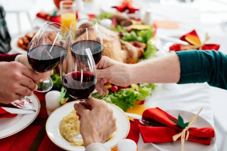 cropped image of family clinking by wine glasses while celebrating thanksgiving at served table with baked turkey