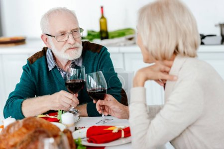 Photo for Senior couple clinking by wine glasses at serve table with baked turkey on thanksgiving - Royalty Free Image