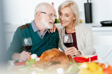 happy senior couple with wine glasses talking at served table for thanksgiving celebration