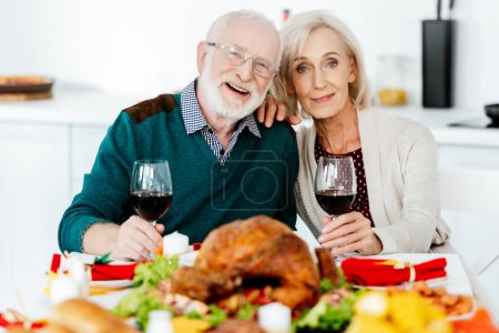 portrait of happy senior couple with wine glasses at served table with delicious turkey on thanksgiving