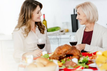 happy adult woman with wine glass talking to senior mother at served table with baked turkey on thanksgiving