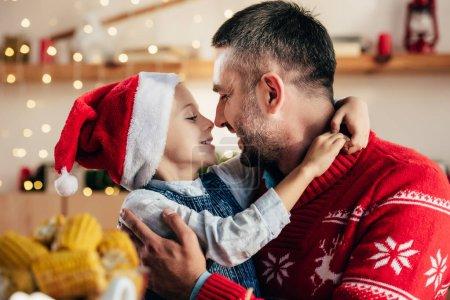 Photo pour Vue latérale du père heureux et de la petite fille dans le chapeau de Noël face à face à la table avec le dîner de vacances - image libre de droit