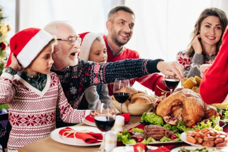 happy senior man pointing at turkey while having christmas dinner with family at home