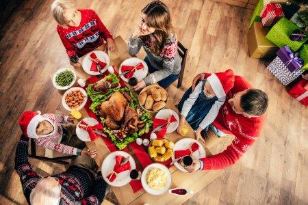 Photo pour Vue aérienne de famille avec petits enfants en ayant des repas de fête à la maison des chapeaux de Noël - image libre de droit