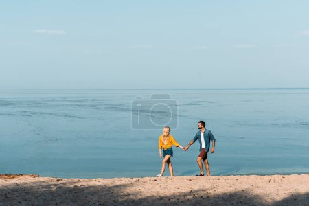 Photo for Couple holding hands and walking on beach - Royalty Free Image