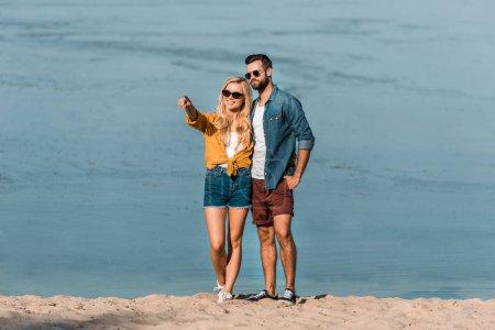 girlfriend pointing on something to boyfriend on beach