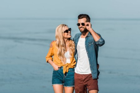 Photo for Smiling couple in sunglasses standing near ocean - Royalty Free Image