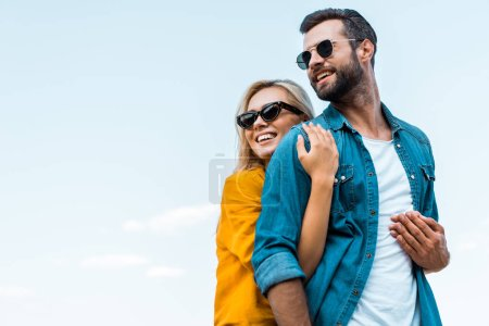 Photo for Low angle view of smiling girlfriend hugging boyfriend against blue sky - Royalty Free Image