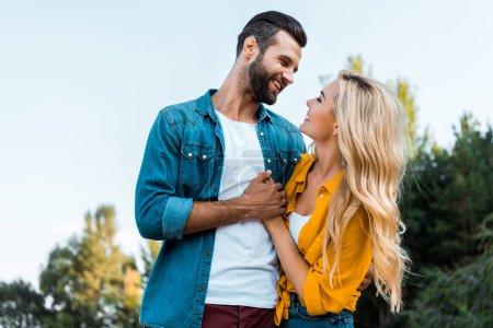 Foto de Feliz pareja cogidos de la mano y mirando el uno al otro en el Parque - Imagen libre de derechos
