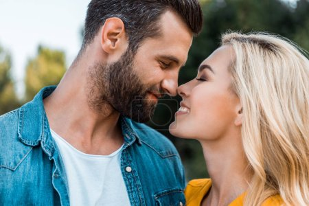 Photo for Portrait of happy couple touching with noses in park - Royalty Free Image