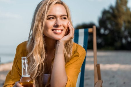 attractive smiling girl sitting on sun lounger with beer in bottle and looking away