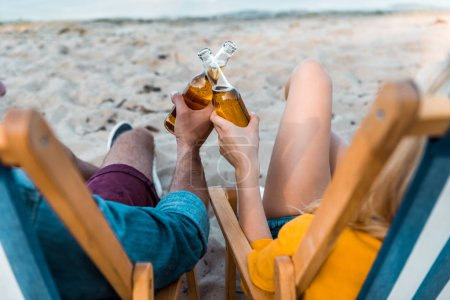 cropped image of couple sitting on sun loungers and clinking with glass bottles of beer on sandy beach