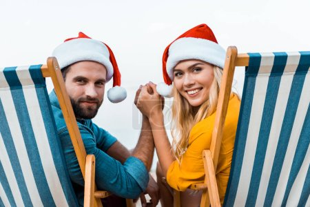 portrait of couple in santa hats sitting on sun loungers, holding hands and looking at camera on beach