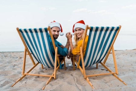 couple in santa hats sitting on sun loungers, holding hands and looking at camera on beach