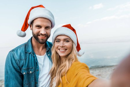 camera point of view of smiling couple in santa hats looking at camera on beach