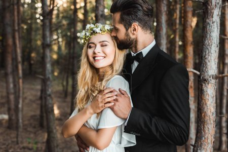 handsome groom hugging beautiful bride with closed eyes in forest