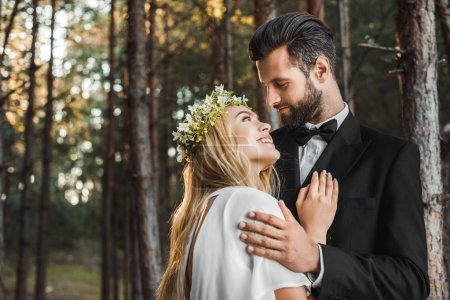 beautiful bride in white dress and handsome groom in suit hugging in forest and looking at each other