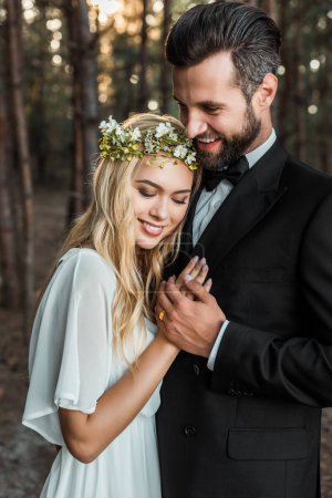 beautiful happy bride in white dress and handsome groom in suit hugging and holding hands in forest