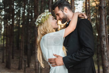 Photo for Beautiful happy bride in white dress and handsome groom in suit hugging and going to kiss in forest - Royalty Free Image
