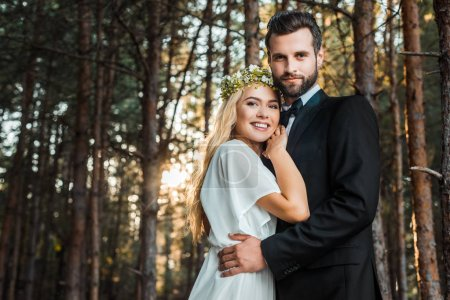 low angle view of smiling wedding couple hugging and looking at camera during sunset in forest